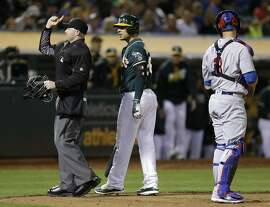 Home plate umpire Mike Estabrook, left, ejects Oakland Athletics' Danny Valencia, center, during the sixth inning of the team's baseball game against the Chicago Cubs on Friday, Aug. 5, 2016, in Oakland, Calif. (AP Photo/Ben Margot)