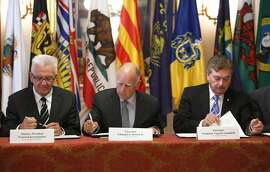 FILE -- In this May 19, 2015 file photo, Gov. Jerry Brown, center, flanked by Baden-Wurttemberg Minister-President Winfried Kretschmann, left, of Germany, and Baja California Gov. Francisco A. Vega de Lamadrid, join others in signing a non-binding climate change agreement in Sacramento, Calif. Diane Boyer-Vine, the chief legal counsel for the California Legislature, says Brown exceeded his authority when he issued an executive order last year setting a new target to reduce California's carbon emissions to 40 percent below 1990 levels by 2030. (AP Photo/Rich Pedroncelli, file)