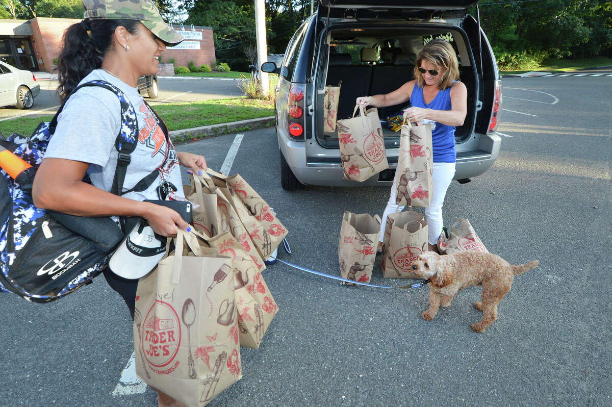 Matina Panagiotidis and Liz Feinstein, moms of Taso and Henry, unload bags of supplies from Trader Joe's for the Norwalk Cal Ripken 10-year-old All-Star team. They had their last practice in Norwalk before heading to the World Series in Florida, on Tuesday, Aug. 2 in Norwalk.