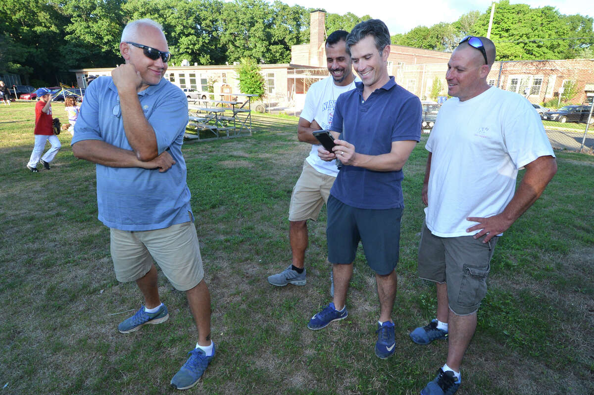 Parents Ken Roberts, John Kodonas, Ken LaFreniere and Keith McNamara look at news footage of the Norwalk Cal Ripken 10-year-old All-Star team. They had their last practice in Norwalk before heading to the World Series in Florida, on Tuesday, Aug. 2 in Norwalk.