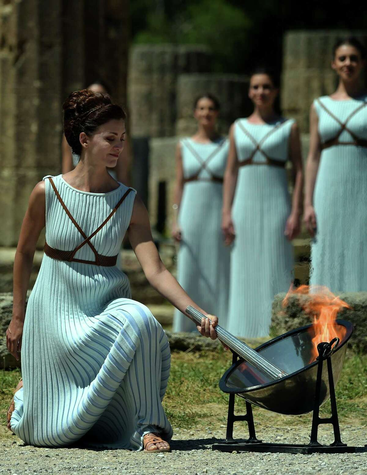 Actress Katerina Lechou acting the high pristess lights the Olympic flame at the Temple of Hera on April 21, 2016 during the lighting ceremony of the Olympic flame in ancient Olympia, the sanctuary where the Olympic Games were born in 776 BC. The Olympic flame was lit Thursday in an ancient temple in one country in crisis and solemnly sent off carrying international hopes that Brazil's political paralysis will not taint the Rio Games that start in barely 100 days. / AFP PHOTO / ARIS MESSINISARIS MESSINIS/AFP/Getty Images