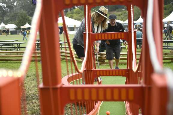 Liz and Joe Streng of Pleasanton play around of wine mini golf at the Outside Lands Music Festival at Golden Gate Park on August 6, 2016 in San Francisco, California.