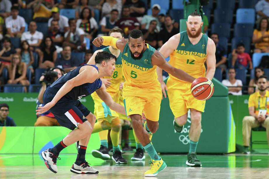 Australia's guard Patty Mills (C) evades France's point guard Thomas Heurtel (L) during a Men's round Group A basketball match between Australia and France at the Carioca Arena 1 in Rio de Janeiro on August 6, 2016 during the Rio 2016 Olympic Games. / AFP PHOTO / Mark RALSTONMARK RALSTON/AFP/Getty Images Photo: MARK RALSTON, AFP/Getty Images / AFP or licensors