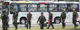 RIO DE JANEIRO, BRAZIL - JULY 30:  Soldiers keep watch in front of a bus before an event inaugurating a new subway station July 30, 2016 in Rio de Janeiro, Brazil. After many delays, the new station on the new Metro Line 4 subway links the Ipanema and Barra da Tijuca neighborhoods, opening just in time for the Rio 2016 Olympic Games. (Photo by Mario Tama/Getty Images)