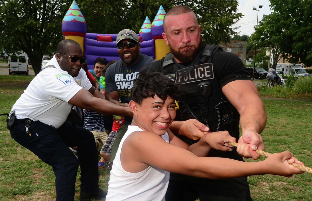 Giancarlo Martel, 13, and OfficerMike Pugliese participate in the tug-o-war as the Norwalk Police Department hosts