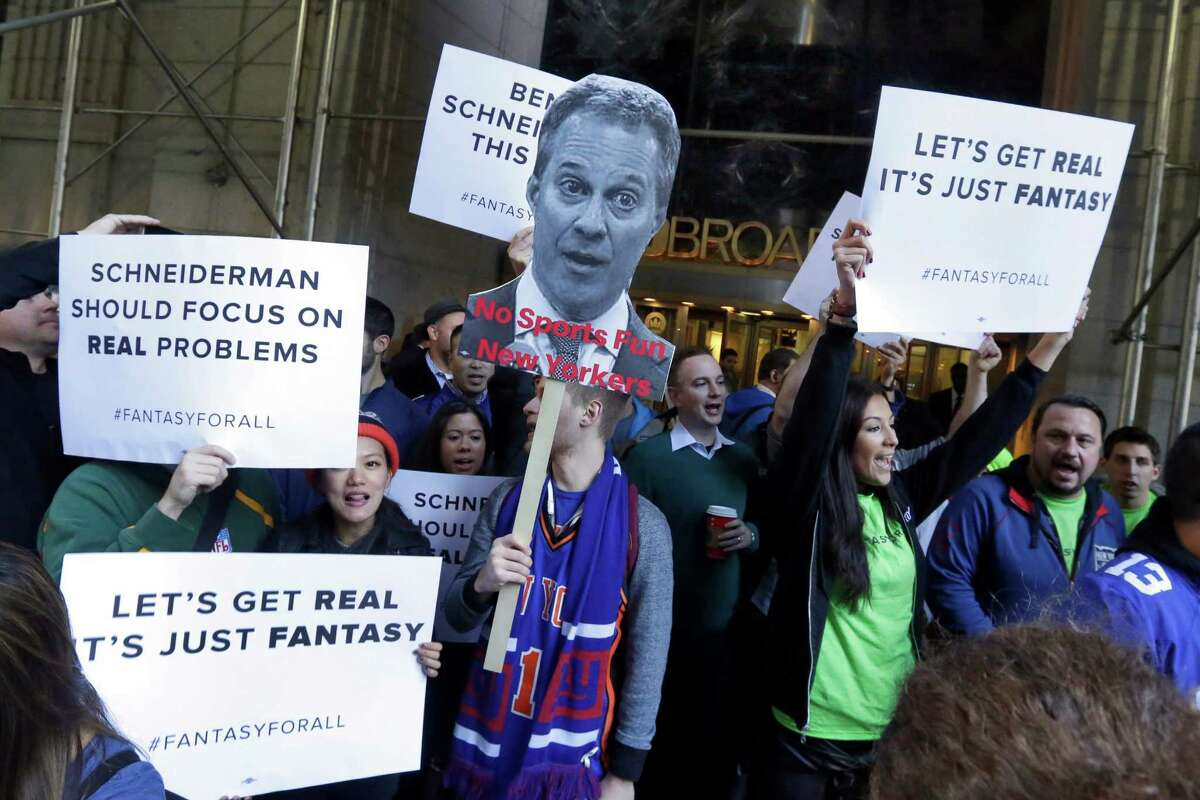 FILE - In this Nov. 13, 2015, file photo, fantasy sports fans demonstrate outside the Financial District offices of New York state Attorney General Eric Schneiderman, in New York. Schneiderman ordered fantasy sports industry giants DraftKings and FanDuel to stop accepting play from New Yorkers, saying their business amounts to illegal gambling. Schneiderman maintains that New York law bans taking bets as a business, with exceptions for horse racing, casinos, state lotteries and certain other settings, but not daily fantasy sports sites. (AP Photo/Richard Drew, File) ORG XMIT: NYR401