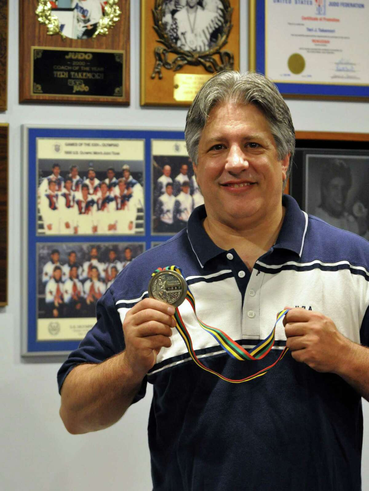 Jason Morris, a 1992 Olympic Silver Medalist in Judo, poses for a photograph with his medal in his office on Friday, Aug. 5, 2016 in Scotia, N.Y. (Eliza Mineaux/Special to the Times Union)