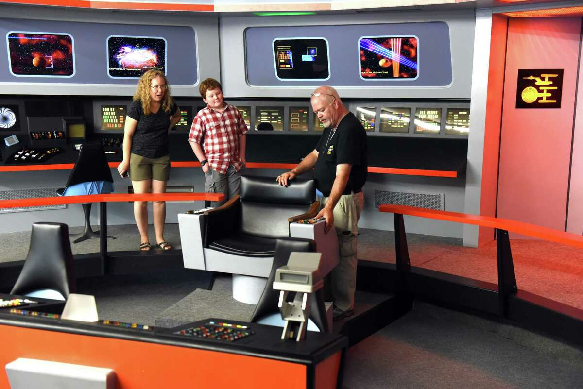 Ken Schmidt gives a tour of the ships bridge to Sandra Niklajevs and her 11-year-old son Peter O'Malley at the Star Trek set on Thursday Aug. 4, 2016 in Ticonderoga, N.Y. (Michael P. Farrell/Times Union)