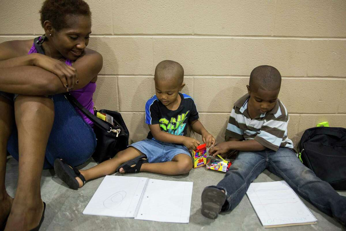 Angela Cox watches her sons Xander Hamilton, 3, and Xavier Hamilton, 4, color while they wait for their older siblings to get haircuts during the annual Back 2 School Expo presented by Alamo Area Colleges at the Freeman Coliseum Expo Hall in San Antonio, Texas on August 6, 2016. Immunizations as well as free school supplies, backpacks and haircuts were all offered during the event, which drew thousands of people.