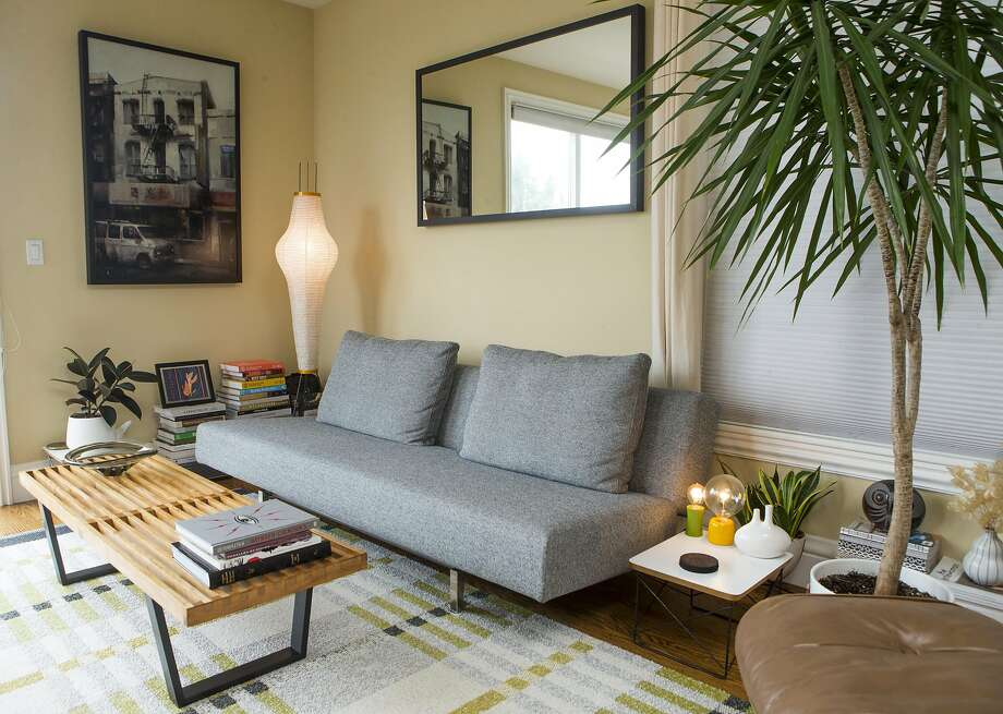 The living room of Kelly Waters and Peter Judd has a Noguchi lamp, painting by Kim Cogan and a gray Bensen sleeper sofa. Photo: Beck Diefenbach, Special To The Chronicle