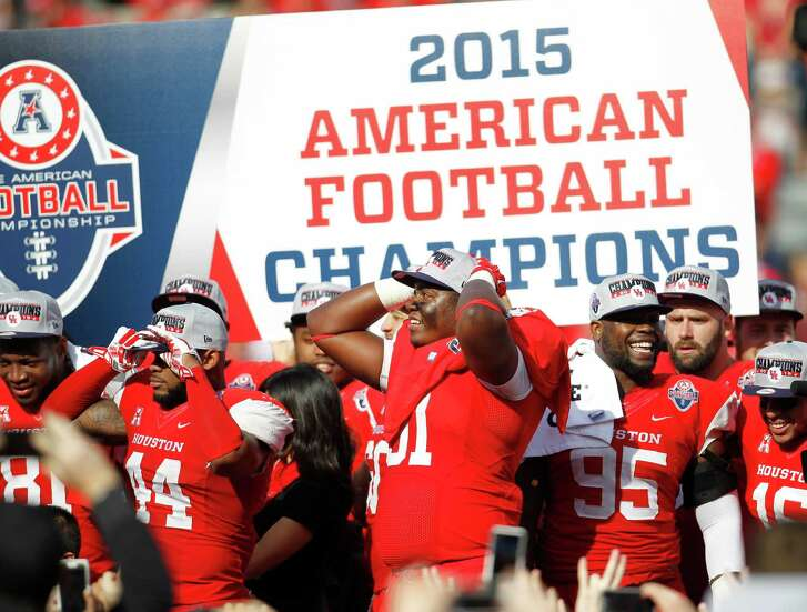 Houston Cougars players stand on the stage with a sea of fans surrounding them on the field after the Cougars 24-13 won over Temple during the American Athletic Conference Championship football game at TDECU Stadium on Saturday, Dec. 5, 2015, in Houston .
