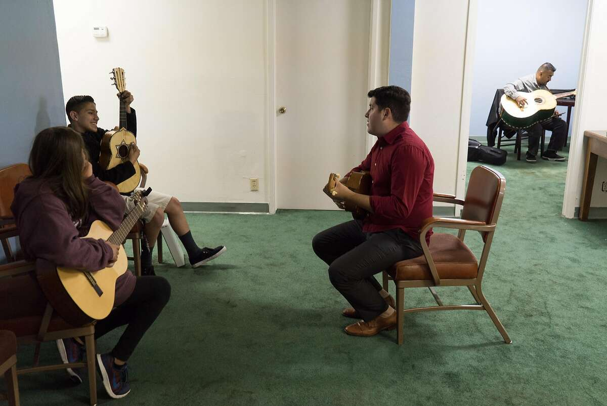 Rene Lambert, second from right, teaches students how to play the Vihuela at the Gilroy Historic Hotel in downtown Gilroy, Calif. on Saturday, Aug. 6, 2016. Felipe Garcia and Jorge Rodriguez learned Mariachi music as children, now they are passing on their knowledge to others through their Mariachi school.