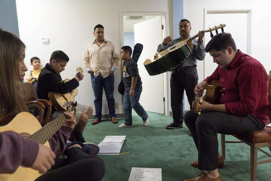 Rene Lambert (right) teaches students traditional mariachi music in Gilroy. Photo: James Tensuan, Special To The Chronicle