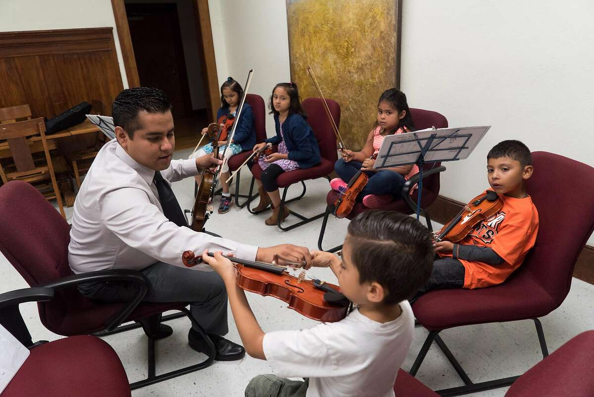 Felipe Garcia teaches students how to play the violin at the Gilroy Historic Hotel in downtown Gilroy, Calif. on Saturday, Aug. 6, 2016. Felipe Garcia and Jorge Rodriguez learned Mariachi music as children, now they are passing on their knowledge to others through their Mariachi school.