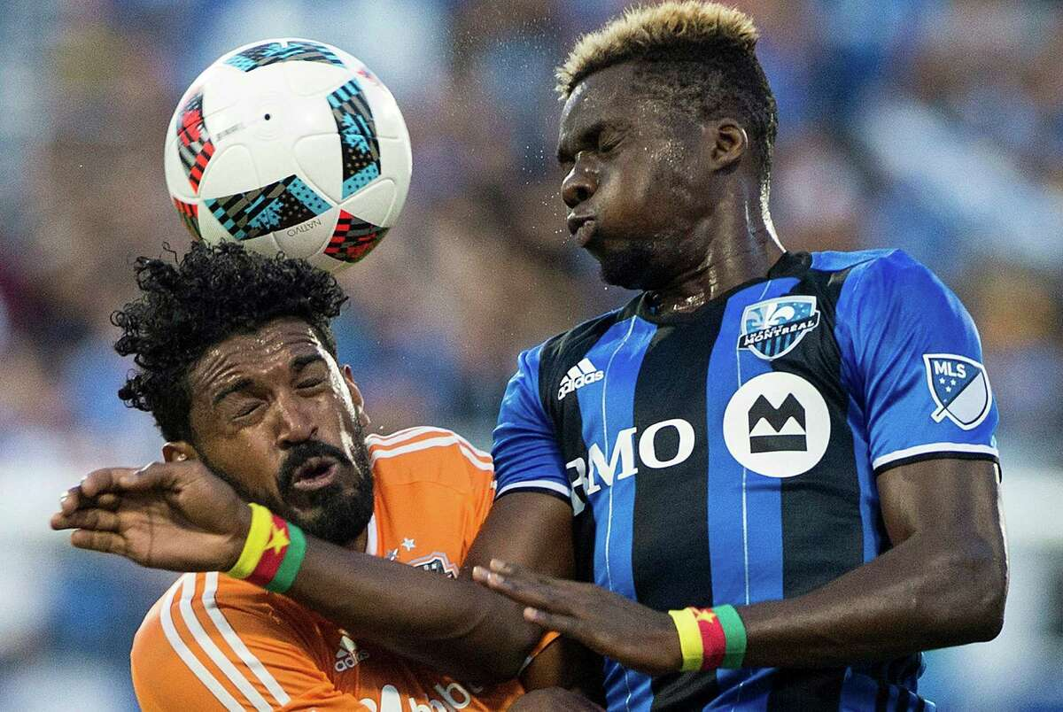 Montreal Impact's Ambroise Oyongo, right, challenges Houston Dynamo's Sheanon Williams during first-half MLS soccer game action in Montreal, Saturday, Aug. 6, 2016. (Graham Hughes/The Canadian Press via AP)