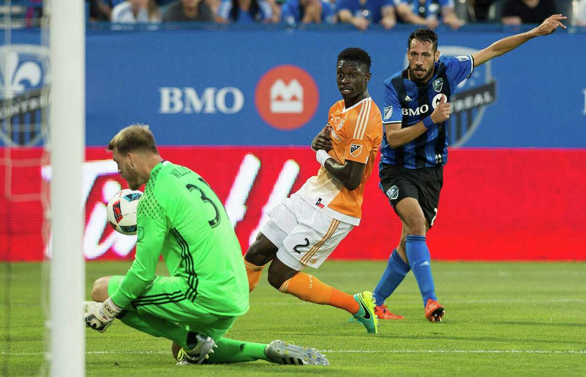 Montreal Impact's Matteo Mancosu, right, shoots at Houston Dynamo's goalkeeper Joe Willis as Dynamo's Jalil Anibaba (2) defends during first-half MLS soccer game action in Montreal, Saturday, Aug. 6, 2016. (Graham Hughes/The Canadian Press via AP)