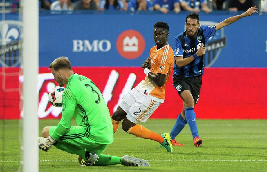 Montreal Impact's Matteo Mancosu, right, shoots at Houston Dynamo's goalkeeper Joe Willis as Dynamo's Jalil Anibaba (2) defends during first-half MLS soccer game action in Montreal, Saturday, Aug. 6, 2016. (Graham Hughes/The Canadian Press via AP) Photo: Graham Hughes, Associated Press / The Canadian Press