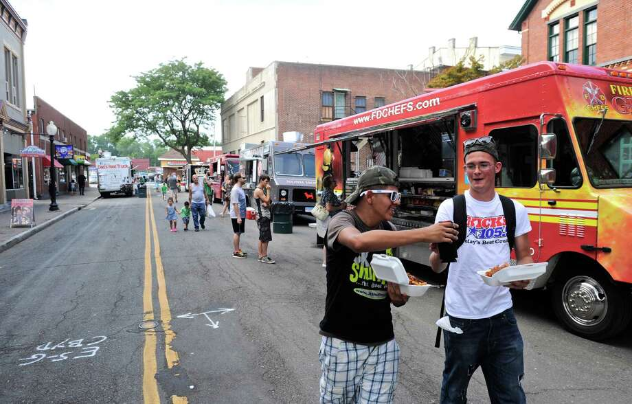 Jesus Muniz, left, and John Fluskey, of Danbury, walk away from one of the food trucks at theCountry Music and Food Truck event on the Green in Danbury, Conn, on Saturday, August 6, 2016 wit their orders of chili fries. Photo: H John Voorhees III / Hearst Connecticut Media / The News-Times