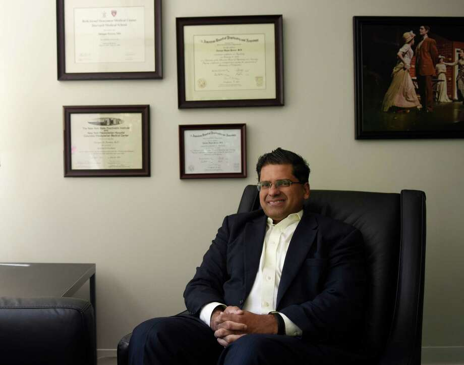 Psychiatrist Tarique Perera, M.D., poses in the office of his practice, Contemporary Care, in Greenwich, Conn. Thursday, Aug. 4, 2016. Contemporary Care has a machine used to perform transcranial magnetic stimulation (TMS), a magnetic method used to stimulate small regions of the brain that can be used to treat depression, anxiety, post-traumatic stress disorder, eating disorders and other mental illnesses. Photo: Tyler Sizemore / Hearst Connecticut Media / Greenwich Time
