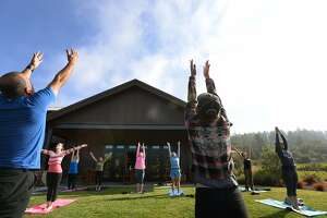 Yoga instructors Chris Coppinger, left, and Mari Coppinger, right, of 2up Yoga, leading a yoga class near the tasting room at Comstock Wines in Healdsburg, California Sunday morning. August 7, 2016.