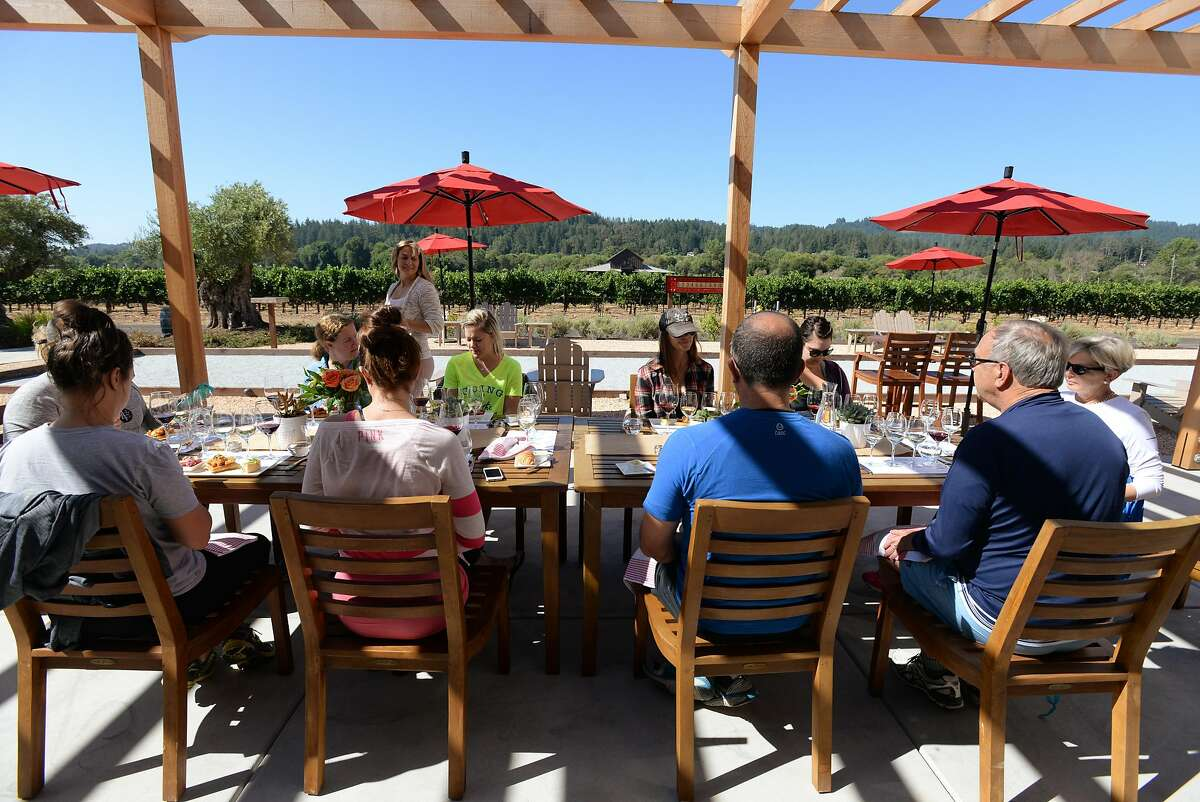 After participating in a yoga class near vineyards guests enjoy a wine flight and food pairing at Comstock Wines in Healdsburg, California Sunday morning. August 7, 2016.
