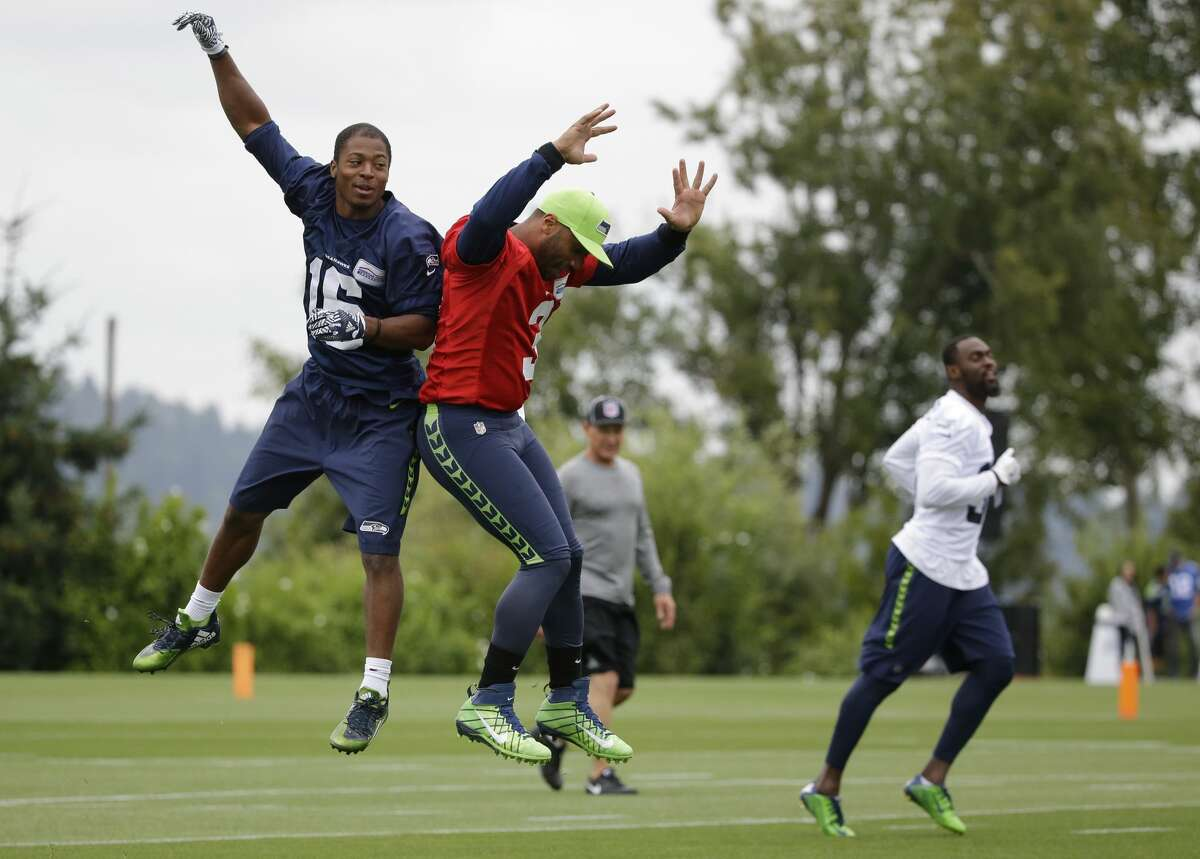 Seattle Seahawks quarterback Russell Wilson, second from left, leaps in with wide receiver Tyler Lockett after Lockett caught a pass from him during NFL football training camp, Saturday, Aug. 6, 2016, in Renton, Wash. (AP Photo/Ted S. Warren)