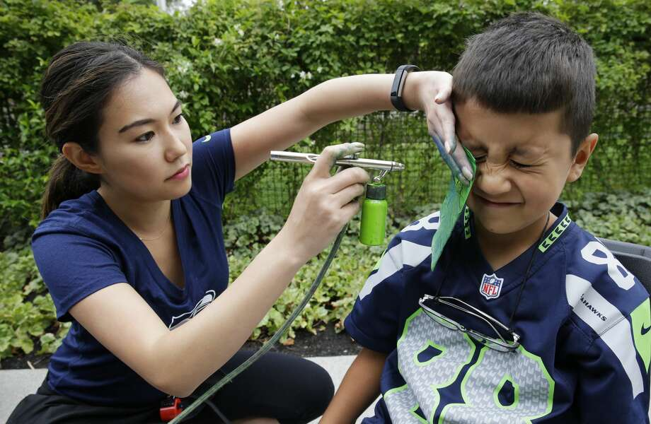 Enrique Guevara, 8, of Renton, Wash., reacts as he has his face painted by Mercedes Luna, left, at a public session of Seattle Seahawks NFL football training camp, Saturday, Aug. 6, 2016, in Renton, Wash. (AP Photo/Ted S. Warren) Photo: Ted S. Warren/AP