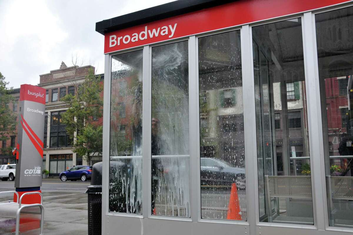 CDTA maintenance worker Brian Gariepy cleans the windows at a CDTA bus shelter on Broadway St. on Monday, Aug. 1, 2016 in Albany, N.Y. (Eliza Mineaux/Special to the Times Union)