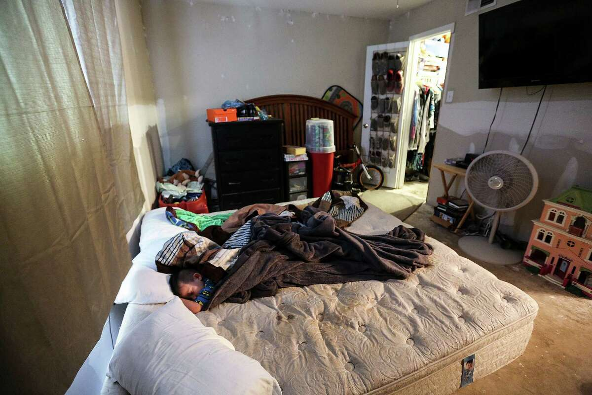 Rylan Garza, 4, sleeps in a bed he shares with his parents in their Greenspoint apartment. The apartment was damaged in April's floods and still hasn't been repaired. Families talk about how life has been since the tax-day floods that displaced many Greenspoint residents on Monday, July 25, 2016, in Houston.