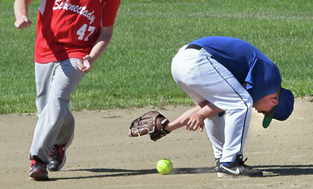 Jude Killar of the Thunderbolts reaches between his legs to retrieve the ball as R.C. Sass of the Schenectady South Paws rounds second base during the Special Olympics New York's 2016 Capital District Local Softball Tournament held at Veterans Memorial Park at Elks Trail on Sunday, Aug. 7, 2016 in Clifton Park, N.Y. (Lori Van Buren / Times Union)