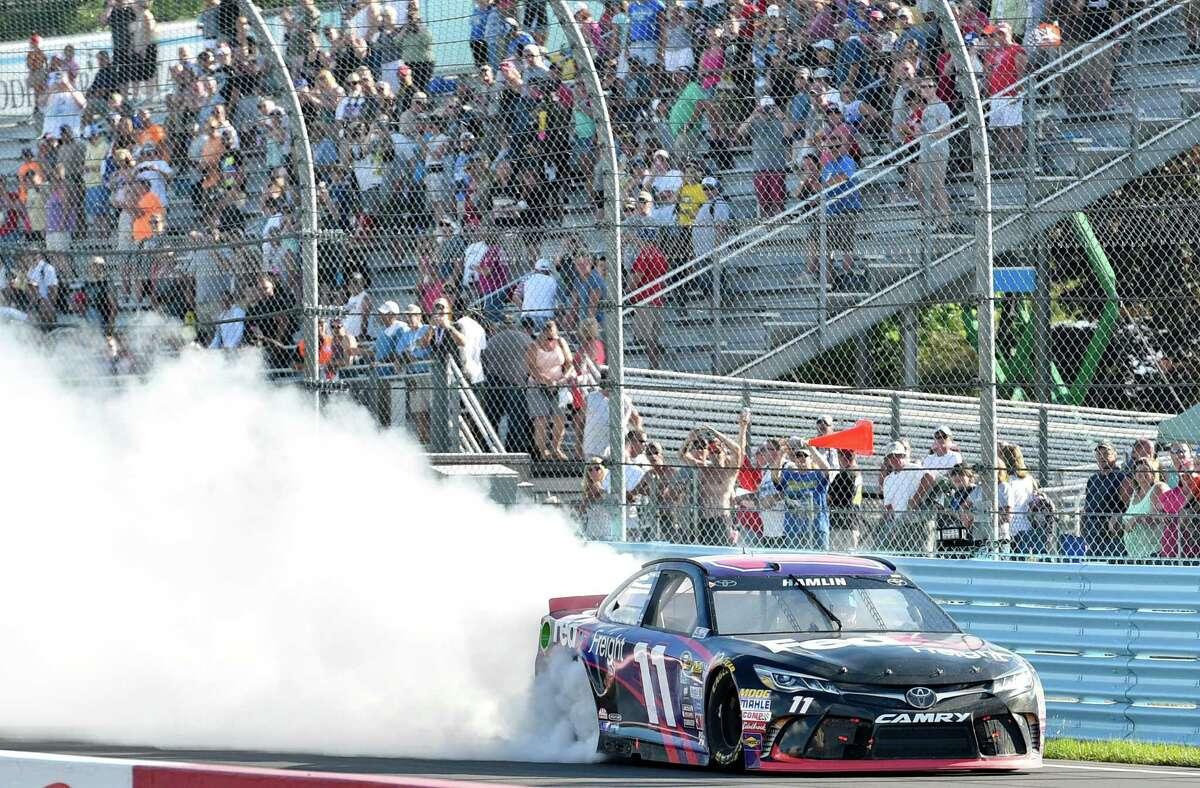 Denny Hamlin celebrates with a burnout after winning a NASCAR Sprint Cup Series auto race at Watkins Glen International, Sunday, Aug. 7, 2016, in Watkins Glen, N.Y. (AP Photo/Derik Hamilton) ORG XMIT: NYDH106