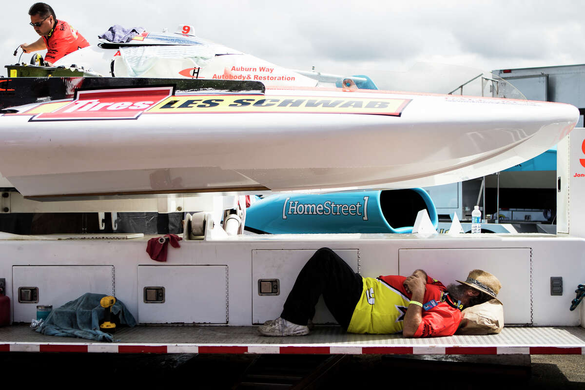 A crew member takes a nap under the Les Schwab hydroplane in the pit during day three of Seafair, Sunday, Aug. 7, 2016. (Lacey Young, seattlepi.com)