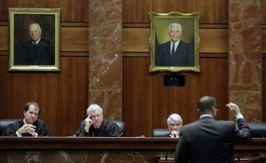 Texas Supreme Court justices, from left, Don Willett, Paul Green, and Nathan Hecht listen as attorney Chad Baruch argues in 2015 in a case for a home-schooling family in El Paso accused of failing to teach its kids anything because they were waiting for the second coming of Jesus Christ. A lawsuit now alleges that electing the court's justices statewide, rather than by district, violates the Voting Rights Act because it all but guarantees Anglos will win. (AP Photo/Eric Gay) Photo: Eric Gay /Associated Press / AP