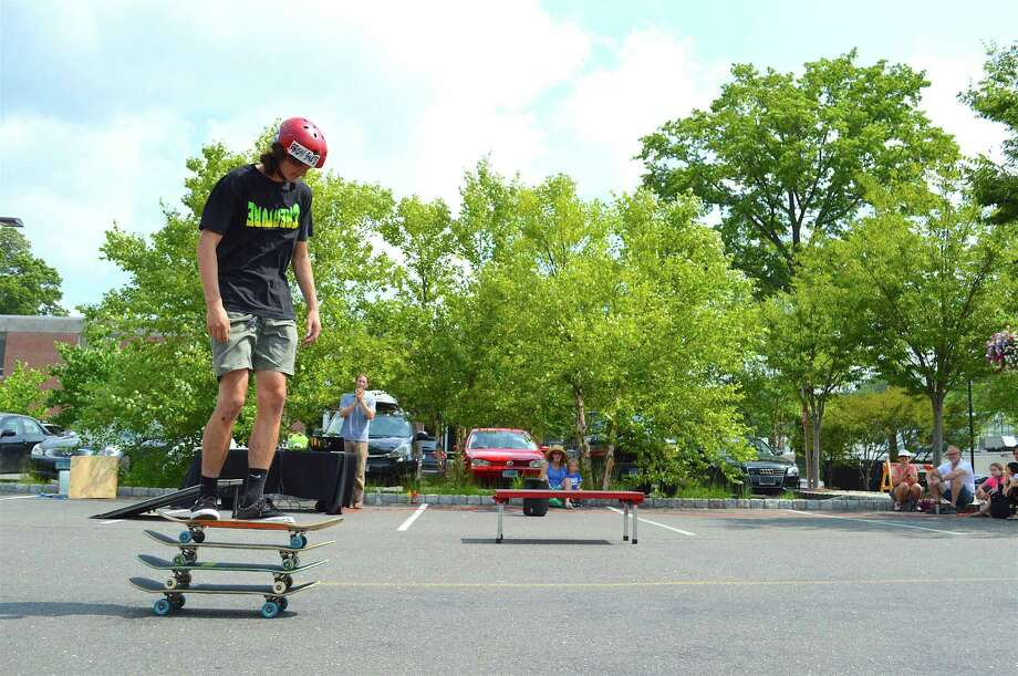 Atop four boards is skater Evan Breder during a science demonstration by the Philadelphia-based company Wondergy at Darien Library Saturday, August 6, 2016, in Darien, Conn. Photo: Jarret Liotta / For Hearst Connecticut Media / Darien News Freelance