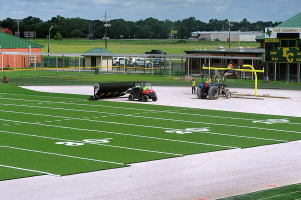 Work crews unroll synthetic turf onto the East Chambers football field on Thursday. Statewide more schools are installing the material in hopes to land more district tournaments at their facility. Photo taken Thursday, August 04, 2016 Guiseppe Barranco/The Enterprise