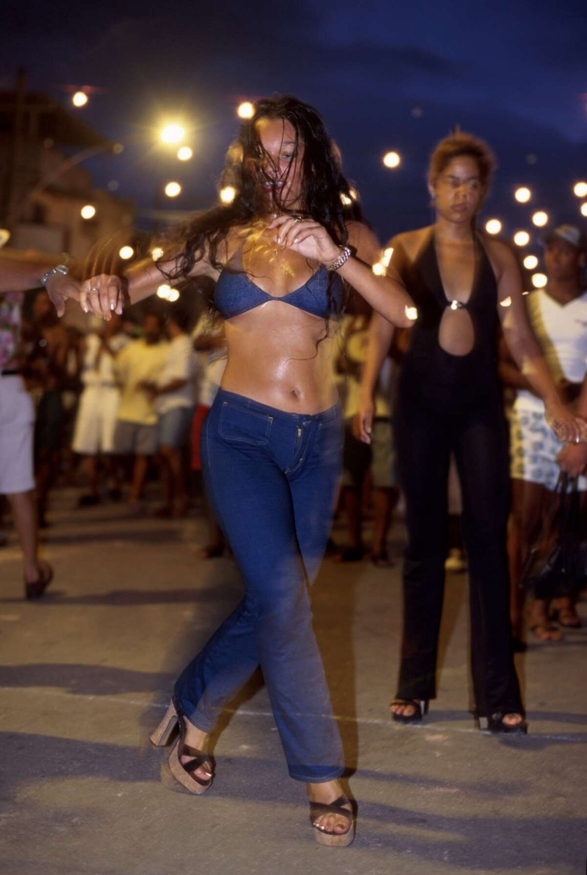 Young and beautiful women dance and have fun in front of Mangueira Samba School headquarter.