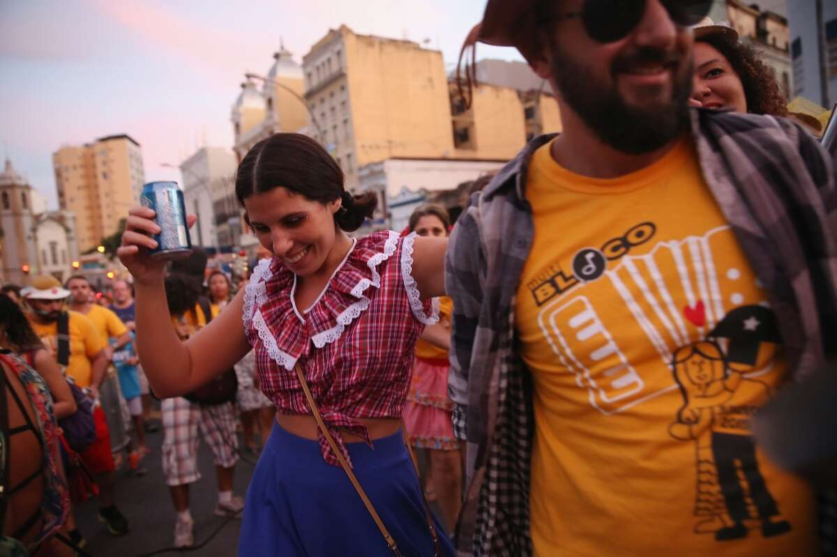 Revelers dance during a 'Festas Juninas' marching performance by the street band 'Monobloco' (C) on July 18, 2015 in Rio de Janeiro, Brazil.
