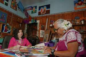 Enedina Vasquez (right) and Jennifer Marie color in faith-themed coloring books. Vasquez, whose home is filled with art and remembrances of her husband, says coloring can make us better listeners.
