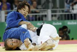 US Marti Malloy (white) competes with Taiwan's Lien Chen-Ling during their women's -57kg judo contest match of the Rio 2016 Olympic Games in Rio de Janeiro on August 8, 2016. / AFP PHOTO / Jack GUEZJACK GUEZ/AFP/Getty Images