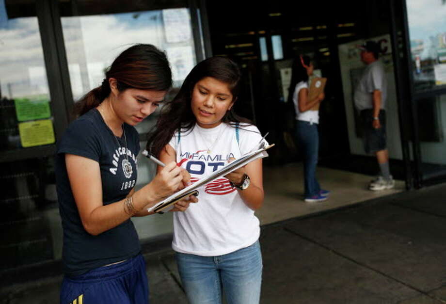 """In this June 9, 2016 photo, Fabiola Vejar, right, registers Stephanie Cardenas to vote in front of a Latino supermarket in Las Vegas. Shielded from deportation under an Obama administration program that protects those brought to the country illegally as children, Vejar, 18, cannot vote. So she volunteers with Mi Familia Vota, encouraging others to be heard at the ballot box. """"I don't have that voice,"""" she says, """"but there's other people ... who feel the way I do. They should vote."""" (AP Photo/John Locher) Photo: John Locher, Associated Press / Copyright 2016 The Associated Press. All rights reserved. This material may not be published, broadcast, rewritten or redistribu"""