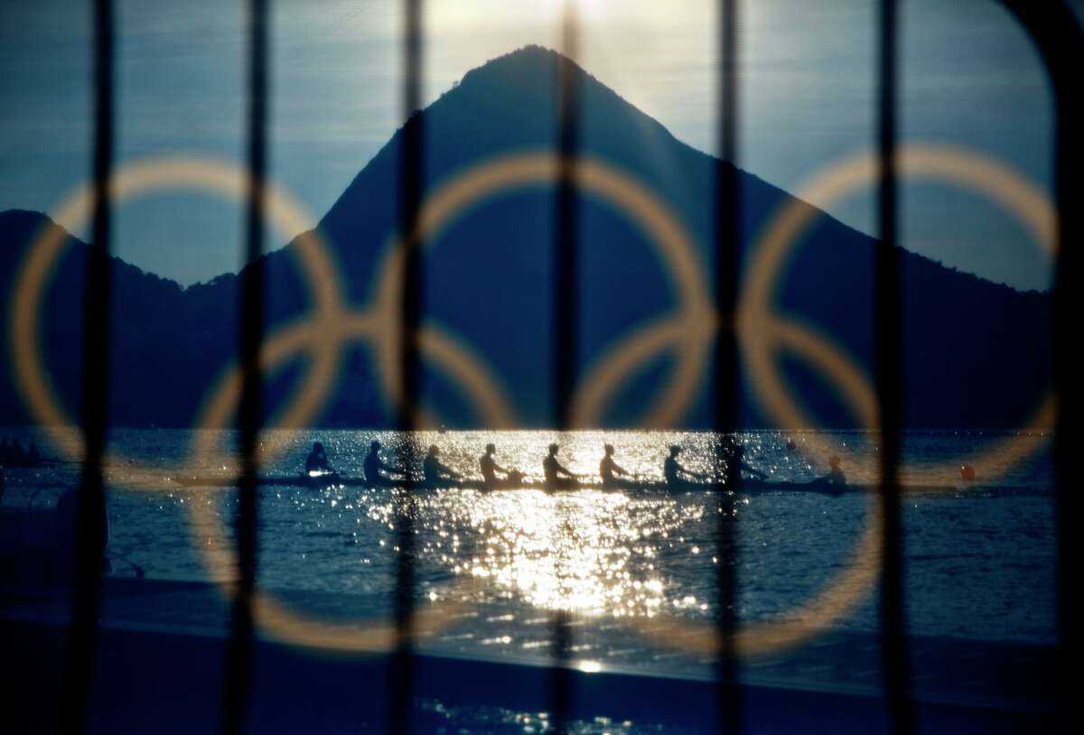 Rowers are seen through a screen decorated with the Olympic rings as they practice at the rowing venue in Lagoa at the 2016 Summer Olympics in Rio de Janeiro, Brazil, Sunday, Aug. 7, 2016.
