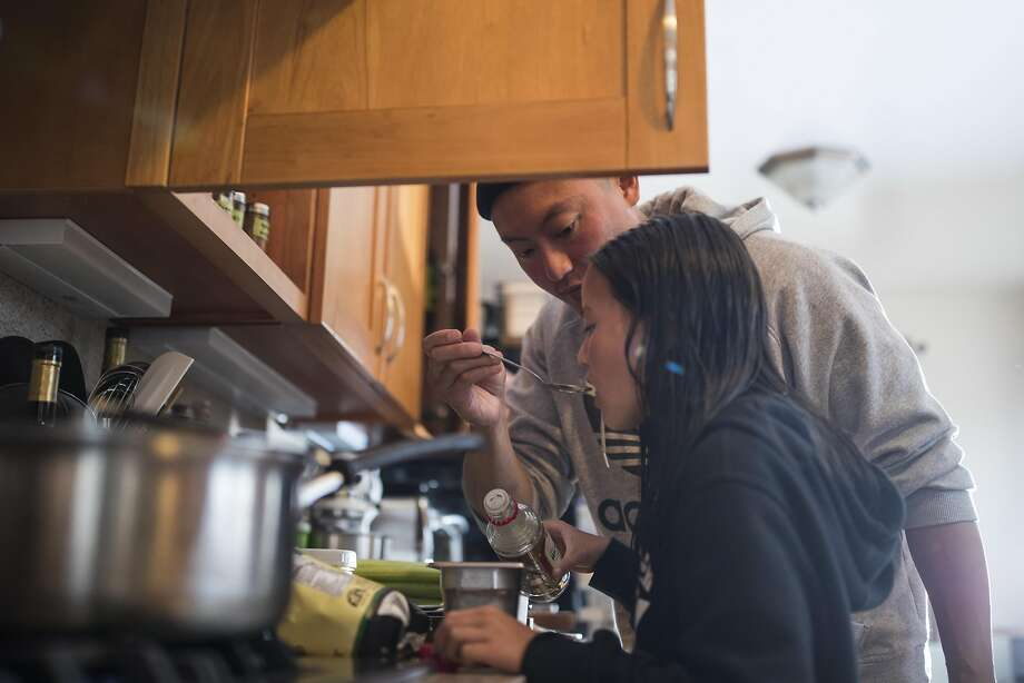 Dennis Lee holds a spoon as his daughter Maya tastes a seasoning they made together for dinner. Photo: Stephen Lam, Special To The Chronicle