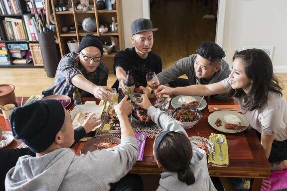 Clockwise from top left, Dennis Lee, David Lee, Jeff Kim, Misa Arnberger, Milla Lee, Dennis Lee and Maya Lee of Namu gaji toast during dinner at their home in San Francisco, Calif. on Thursday, Aug. 4, 2016.