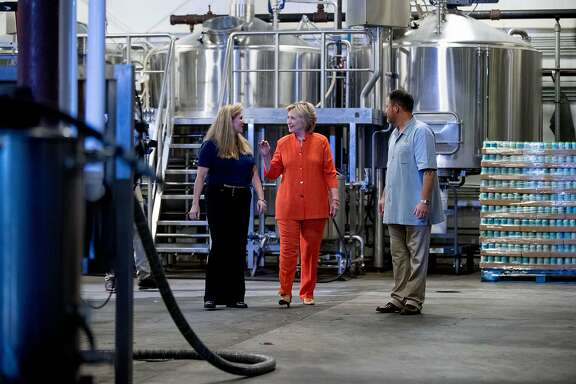Democratic presidential candidate Hillary Clinton tours 3 Daughters Brewery with founder and co-owner Mike Harting, right, and co-owner Leigh Harting, left, in St. Petersburg, Fla., Monday, Aug. 8, 2016. (AP Photo/Andrew Harnik)