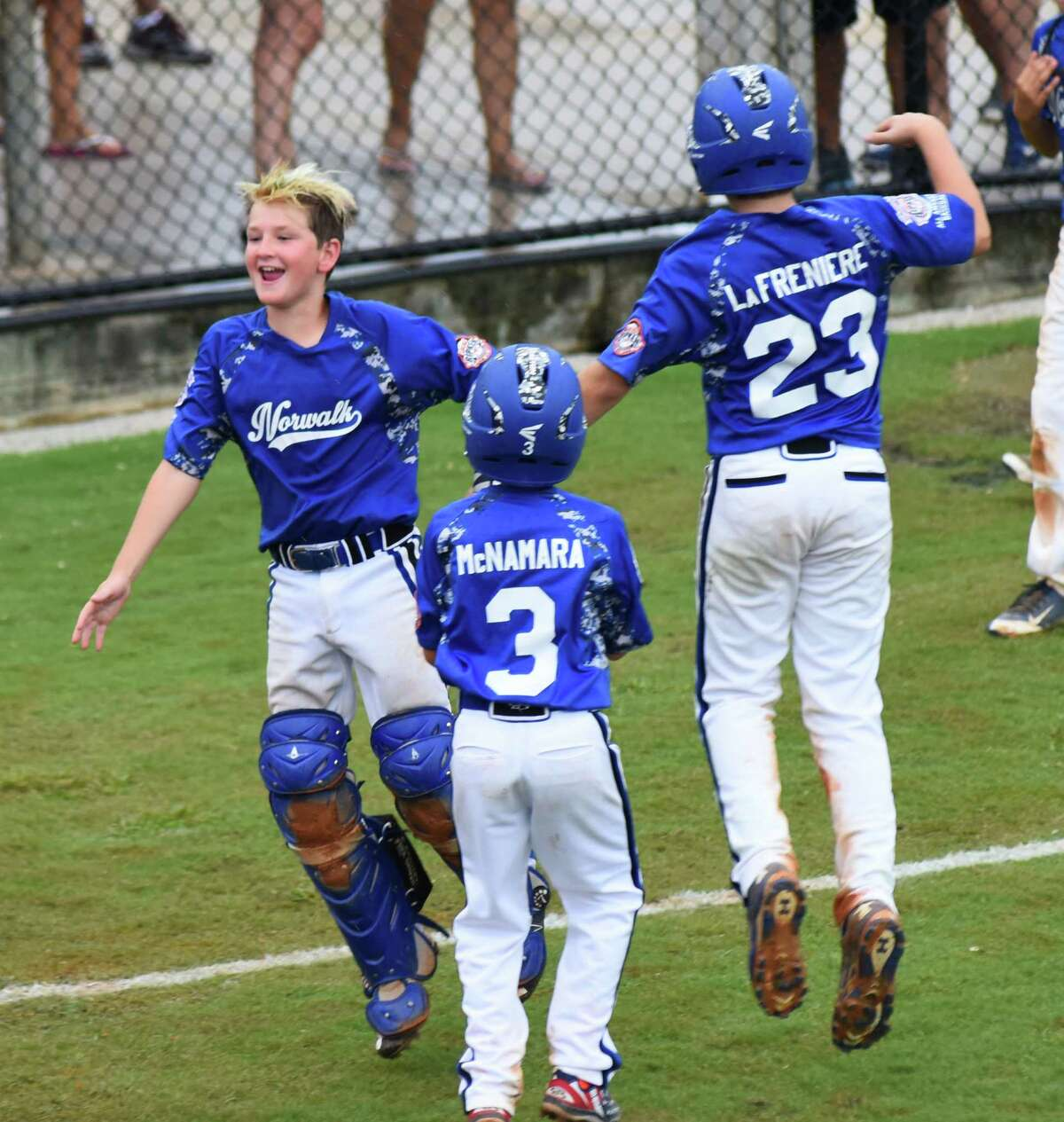 Norwalk's Keegan Cullen, left, Charlie LaFreniere, right, and Andrew McNamara, center, celebrate LaFreinere's game-clinching two-run single at the end of Monday's 13-3 Cal Ripken 10-year-old World Series game against Bryant, Ark., at Gardens Park in Palm Beach Gardens, Fla.