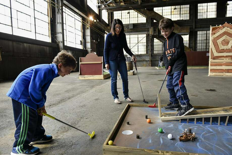 Ethan Pearlmutter (right) and mom Lisa Pearlmutter watch as Ari Pearlmutter putts his ball at Pier 70 Putt Putt in San Francisco. Photo: Michael Short, Special To The Chronicle