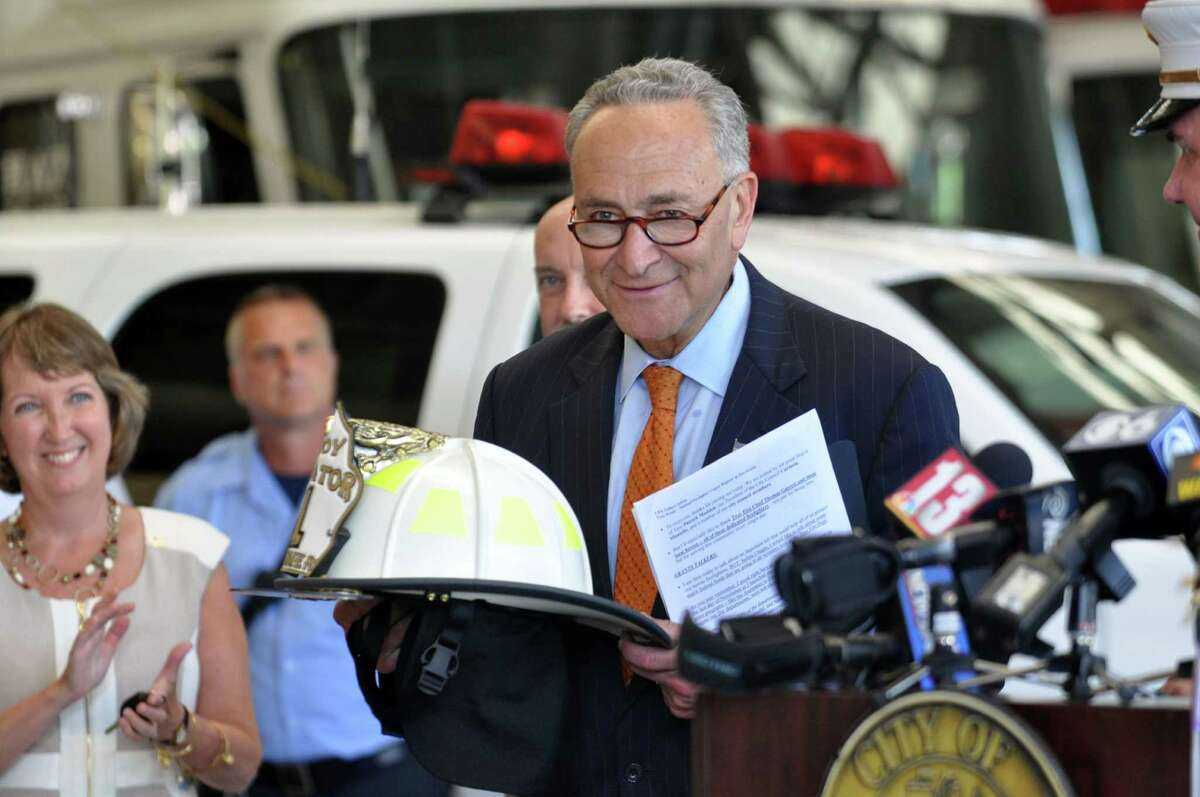 U.S. Senator Charles E. Schumer receives his own firefighter hat from the Troy Fire Chief Thomas Garrett on Monday, Aug. 8, 2016, at the Troy Central Fire House in Troy, N.Y. (Eliza Mineaux/Special to the Times Union)