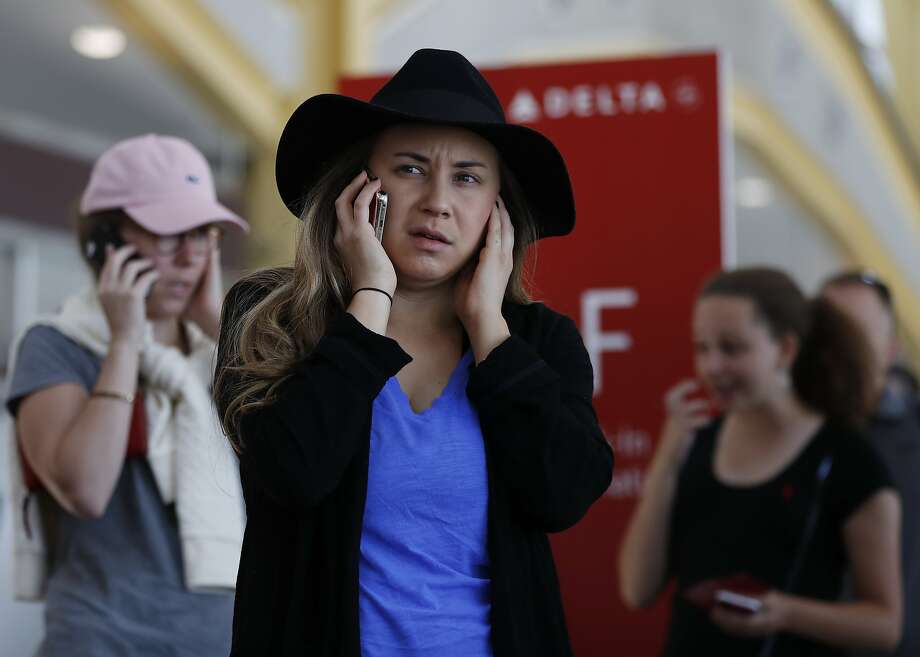 Jenna Raspanti and other travelers talk on their cell phones as they stand in line at the Delta ticketing counter at Washington's Ronald Reagan Washington National Airport, Monday, Aug. 8, 2016. Raspanti is trying to get to San Francisco after her Delta flight was delayed. Delta Air Lines delayed or canceled hundreds of flights Monday after its computer systems crashed, stranding thousands of people on a busy travel day. Photo: Carolyn Kaster, Associated Press