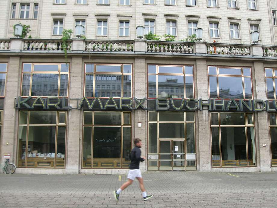 A runner passes the Karl Marx Buchhandlung (bookstore) in a part of town that once was East Berlin. Photo: David Farley, Special To The Chronicle