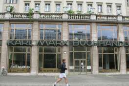 A runner passes the Karl Marx Buchhandlung (Bookstore) in a part of town that once was East Berlin.